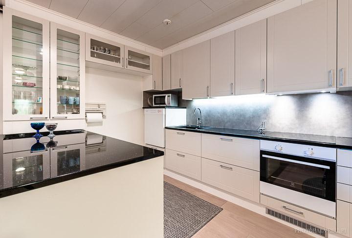 Asunnon myyntikuva keittiöstä jossa on tumma taso ja valkoiset kaapistot