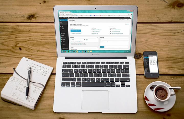 Kannettava tietokone, vihko ja kahvikuppi pöydällä nettisivujen suunnittelua varten